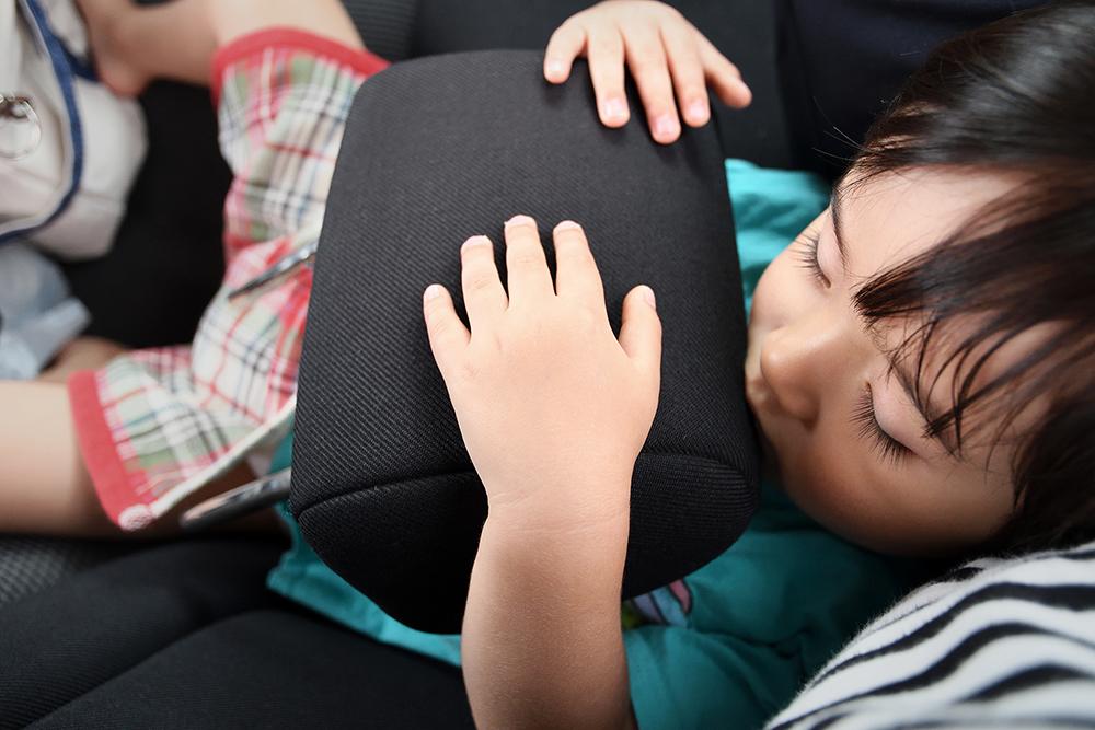 ヘッドレストを持って昼寝する息子